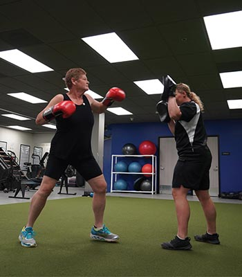 Kristi boxing with her trainer